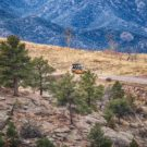 distant view of Colorado Jeep driving with mountains in background