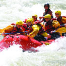 family and guide navigating waves on whitewater rafting tour