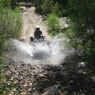 Play Dirty ATV rider splashes though water during a tour Royal Gorge Canon City Colorado