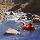 two guests and guide through calm waters on rafting tour